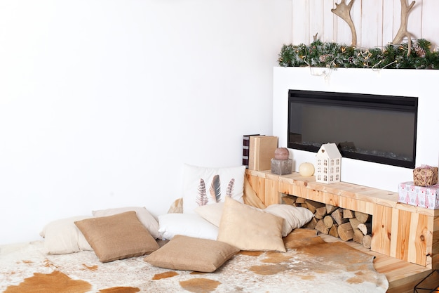 Stylish christmas scandinavian minimalistic interior with an elegant sofa. comfort home. modern country house interior with wooden bed, firewood, fireplace.