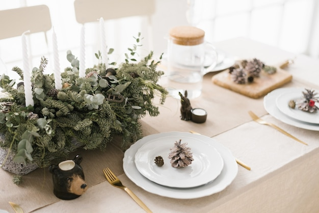 スタイリッシュなクリスマステーブルセッティング:モミの枝、コーンで飾られた白いプレートの構成