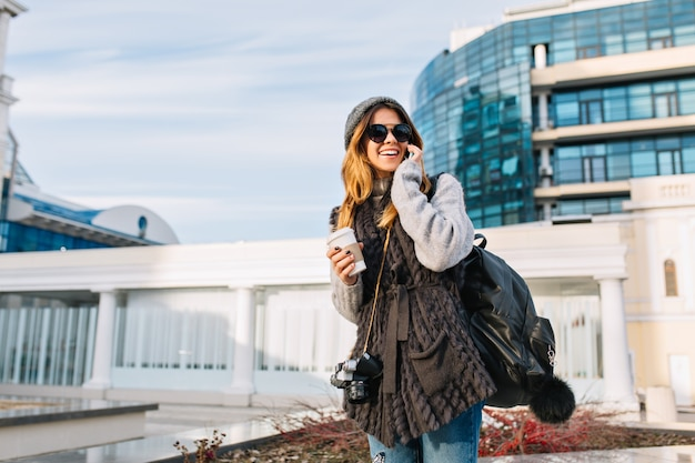 Stylish city portrait of fashionable pretty girl, walking with coffe in modern europe city centre. joyful young woman in winter warm sweater