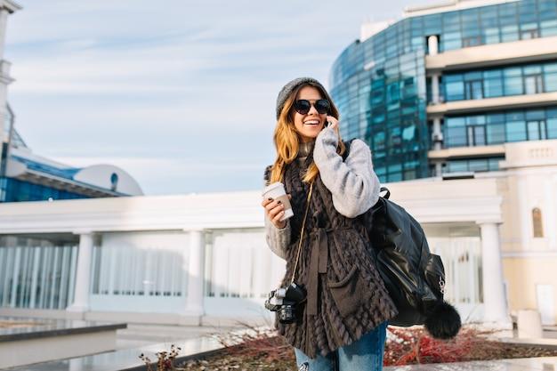 現代ヨーロッパの市内中心部でコーヒーと歩いて、ファッショナブルなかわいい女の子のスタイリッシュな街の肖像。冬の暖かいセーターでうれしそうな若い女性