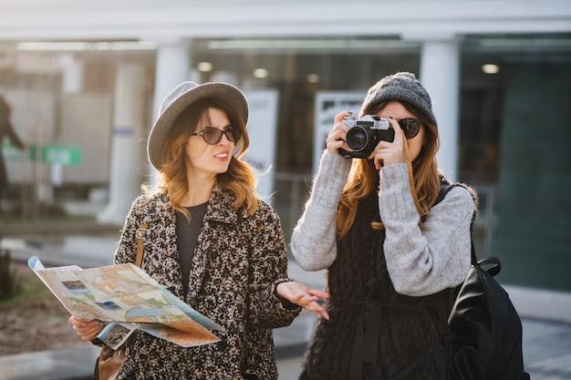 Стильный городской портрет двух модниц, идущих в центре современного города европы. модные друзья путешествуют с рюкзаком, картой, фотоаппаратом, делают фото, туристы, теряются.