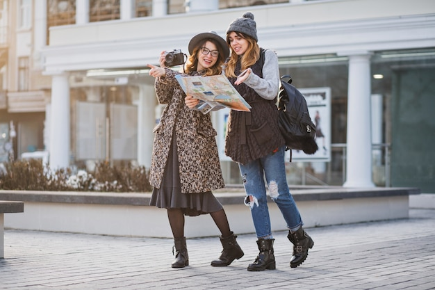 Stylish city portrait of two fashionable women walking in europe modern city centre. fashionable friends travelling with backpack, map, camera, making photo, tourist, get a lost, place for text.