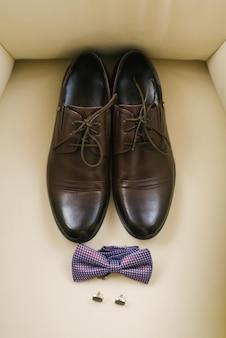 베이지 색 배경에 끈, 격자 무늬 나비 넥타이와 커프스 단추가있는 세련된 클래식 남성용 신발. 결혼식에서 신랑을위한 액세서리