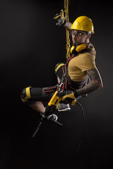 The stylish climber builder hands and works with the tool. black background. copy past