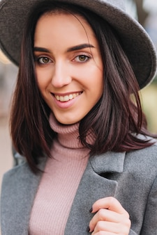 通りを歩いてブルネットの髪を持つスタイリッシュなクローズアップの肖像画かなり若い女性。灰色の帽子、コート、豪華な服、エレガントな外観、陽気な気分、笑顔。