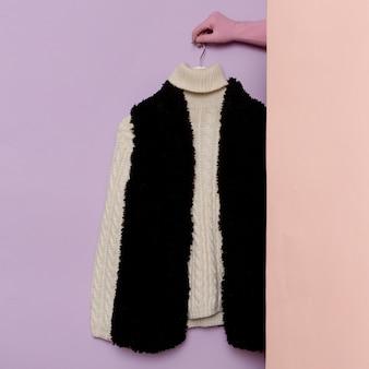 세련된 옷. 따뜻한 스웨터와 모피 조끼. 옷장 아이디어 트렌드