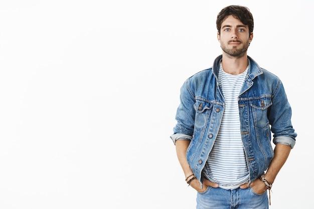 时髦的和cofnident英俊的年轻人有胡子和蓝眼睛的牵胎在口袋里的手在灰色墙壁上在时髦牛仔布夹克微笑在汽车附近的夹克妇女朋友