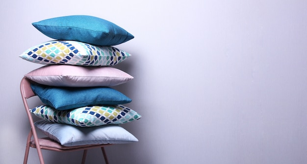 Stylish colorful pillows in room on grey wall . dark blue,pink,blue cushions on the chair.copy space,cozy home concept.