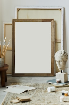 Stylish composition of artist workspace with mock up poster frame, painitng accessories, carpet decor,  decoration and notes. template.