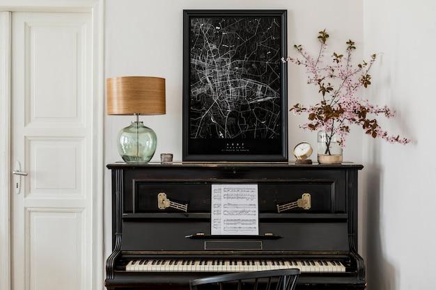 Стильная композиция в интерьере гостиной с черным пианино, макетом карты плаката, засушенными цветами, часами, книгой, лампой, белой стеной и элегантными личными аксессуарами в современном домашнем декоре.