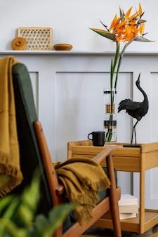 Стильная композиция в интерьере гостиной с дизайнерским креслом, пледом, растением, чашкой кофе, цветком в вазе, книгой, деревянными панелями с полкой и элегантными личными аксессуарами в современном домашнем декоре.