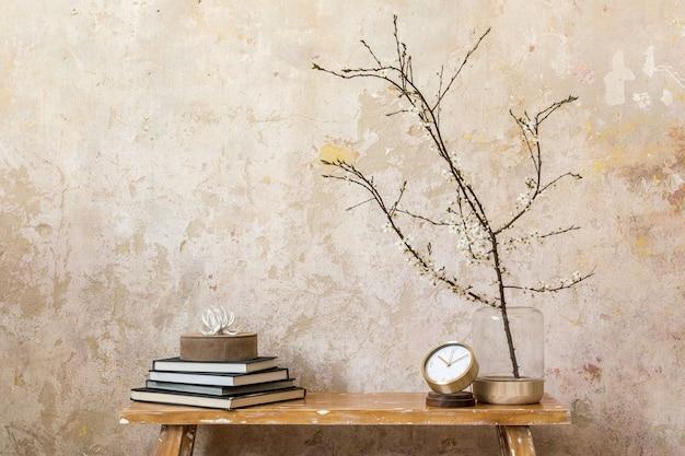 Стильная композиция в интерьере гостиной с дизайнерскими часами, деревянной скамейкой, сухоцветами в вазе, гранжевой стеной и элегантными личными аксессуарами в современном домашнем декоре. скопируйте пространство.
