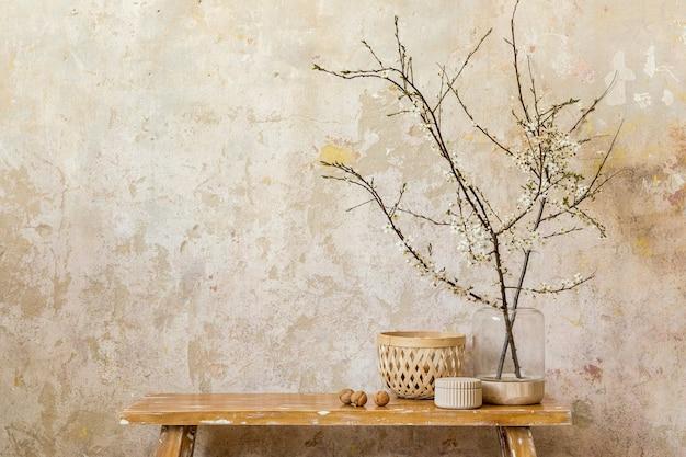 デザインの木製ベンチ、花瓶のドライフラワー、グランジの壁、ボックス、モダンな家の装飾のエレガントなパーソナルアクセサリーを備えたリビングルームのインテリアのスタイリッシュな構成。スペースをコピーします。