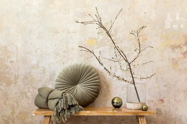 木製のベンチ、花瓶のドライフラワー、グランジの壁、格子縞、枕、モダンな家の装飾のエレガントなパーソナルアクセサリーを備えたリビングルームのインテリアのスタイリッシュな構成。スペースをコピーします。