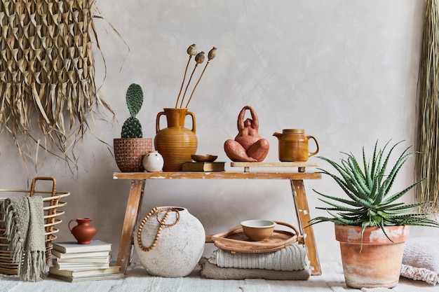 Stylish composition of cozy living room interior with copy space, bench in retro style, clay vase, crockery, straw wall decoration and textiles. rustic inspiration. summer vibes. beige wall. template.