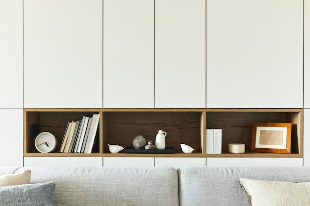 Stylish composition of creative living room interior details such as books, clocks and other personal accessories. white pannels. kitchen on the background. details. template.