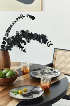 Stylish composition on the design table with elegant plates, glasses, fruits and black eucalyptus flowers in wooden vase. modern dining room interior.