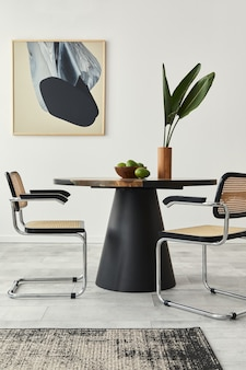 Stylish composition of dining room interior with design table, modern chairs, decoration, tropical leaf in vase, fruits, abstract paintings and elegant accessories in home decor.