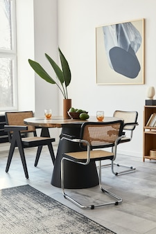 Stylish composition of dining room interior with design table, modern chairs, decoration, tropical leaf in vase, fruits, bookcase, abstract paintings and elegant accessories in home decor.