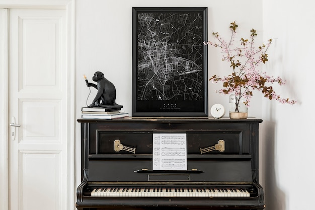 Stylish composition at living room interior with black piano, poster map, dried flowers and elegant presonal accessories in modern home decor.