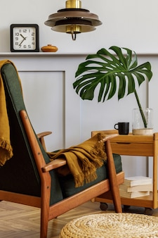 Stylish composition at living room interior with design armchair, plaid, clock, cup of coffeee, laves in vase, book, wood panels with shelf and elegant personal accessories in modern home decor.