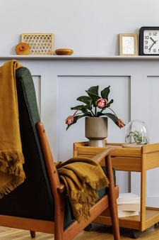 Stylish composition at living room interior with design armchair, plaid, clock, plant, air plant, book, wood panels with shelf and elegant personal accessories in modern home decor.