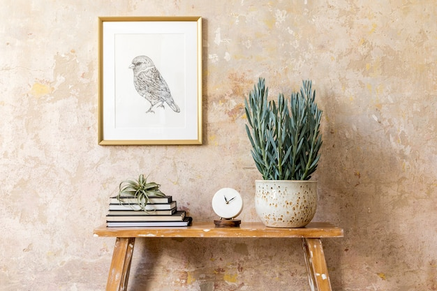 Stylish composition of living room interior with gold mock up frame, wooden bench, clock, plants, air plant, book, grunge wall and elegant personal accessories in modern home decor.