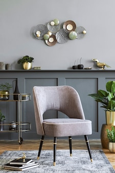 Stylish composition of living room with design gray armchair, gold liquor cabinet, plants and elegant personal accessories. gray wall panelling with shelf. modern home decor.