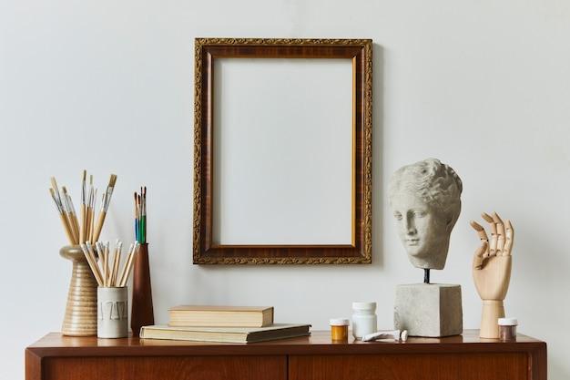 デザインレトロチーク便器、ポスターフレーム、本、装飾、絵画アクセサリーを備えたアーティストワークスペースルームのスタイリッシュな構成。