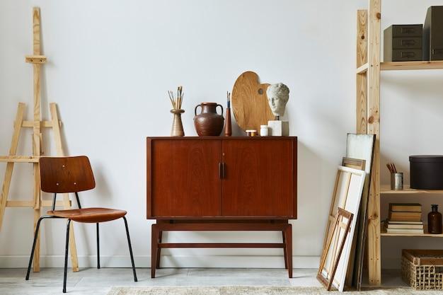 Стильная композиция рабочего места художника с дизайнерским комодом из тикового дерева в стиле ретро, стулом, книжным шкафом, рамами, мольбертом, декором и элегантными личными аксессуарами.