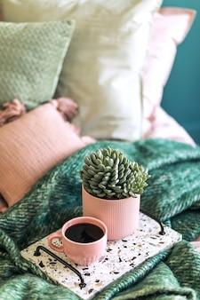 コーヒーとエレガントなパーソナルアクセサリーを備えたラストリコトレイを備えた寝室のインテリアのスタイリッシュな構成。美しいピンクとグリーンのベッドシーツ、毛布、枕。ホームステージングを設計します。閉じる