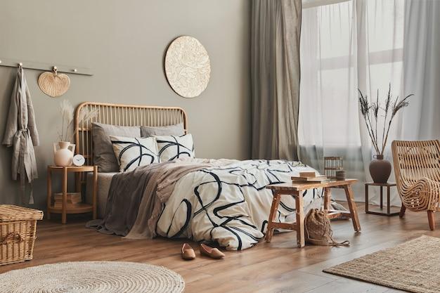 木製のベッド、家具、花瓶のドライフラワー、籐の装飾、花瓶、エレガントなアクセサリーを備えた寝室のインテリアのスタイリッシュな構成
