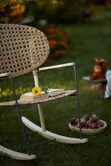 Стильная композиция загородного сада с дизайнерским креслом из ротанга, деревянной скамейкой, пледом, едой, напитками и элегантными аксессуарами. много ярких цветов. летнее настроение.