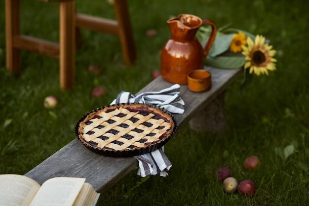 古い木製のベンチ、本、ヒマワリ、ケーキ、セラミックジャー、エレガントなアクセサリーを備えた田舎の庭のスタイリッシュな構成。色とりどりの花がたくさん。夏の気分。テンプレート。