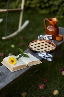 오래된 나무 벤치, 책, 해바라기, 케이크, 세라믹 항아리 및 우아한 액세서리가있는 시골 정원의 세련된 구성. 화려한 꽃이 많이. 여름 분위기.