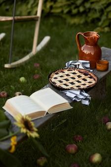 Стильная композиция загородного сада со старой деревянной скамейкой, книгой, подсолнухом, тортом, керамической банкой и элегантными аксессуарами. много ярких цветов. летнее настроение.