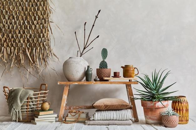 コピースペース、レトロなスタイルのベンチ、粘土の花瓶、食器、わらの壁の装飾とテキスタイルを備えた居心地の良いリビングルームのインテリアのスタイリッシュな構成。素朴なインスピレーション。夏の雰囲気。ベージュの壁。レンプレート。