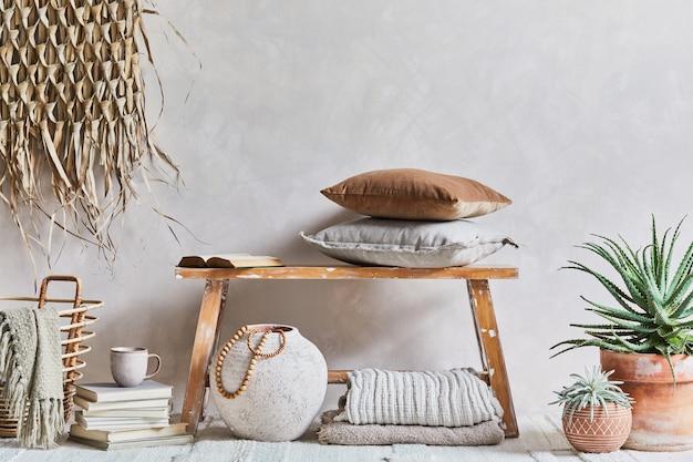 복사 공간이 있는 아늑한 거실 인테리어의 세련된 구성, 복고풍의 벤치, 점토 꽃병, 그릇, 밀짚 벽 장식 및 직물. 소박한 영감. 여름 분위기. 베이지색 벽. 주형.