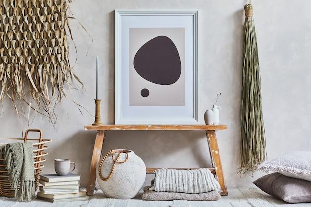 모의 포스터 프레임, 복고 스타일의 벤치, 점토 꽃병, 그릇, 짚으로 장식된 아늑한 거실 인테리어의 세련된 구성. 소박한 영감. 여름 분위기. 베이지색 벽. 주형.