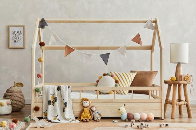 木製のベッド、枕、エレガントなランプ、ぬいぐるみ、木のおもちゃ、テキスタイルの吊り下げ装飾が施された、居心地の良いスカンジの子供部屋のインテリアのスタイリッシュな構成。創造的な壁、床のカーペット。レンプレート。