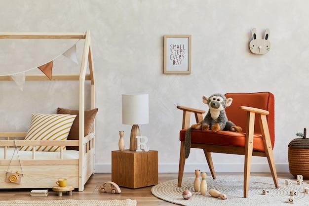 ベッド、赤いアームチェア、ぬいぐるみと木のおもちゃ、テキスタイルの吊り下げ装飾が施された居心地の良いスカンジナビアの子供部屋のインテリアのスタイリッシュな構成。創造的な壁、床のカーペット。スペースをコピーします。レンプレート。