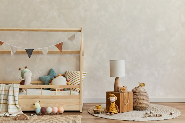 ベッド、木製の立方体、ぬいぐるみ、木のおもちゃ、テキスタイルの吊り下げ装飾が施された居心地の良いスカンジナビアの子供部屋のインテリアのスタイリッシュな構成。創造的な壁、床のカーペット。スペースをコピーします。レンプレート。