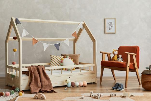 木製のベッド、アームチェア、ぬいぐるみ、木のおもちゃ、テキスタイルの吊り下げ装飾が施された、居心地の良いスカンジナビアの子供部屋のインテリアのスタイリッシュな構成。ニュートラルなクリエイティブウォール。レンプレート。