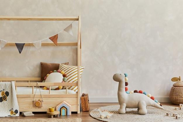 木製のベッド、枕、豪華な恐竜、木のおもちゃ、テキスタイルの装飾が施された居心地の良いスカンジナビアの子供部屋のインテリアのスタイリッシュな構成。中立的な壁、床にカーペット。スペースをコピーします。レンプレート。