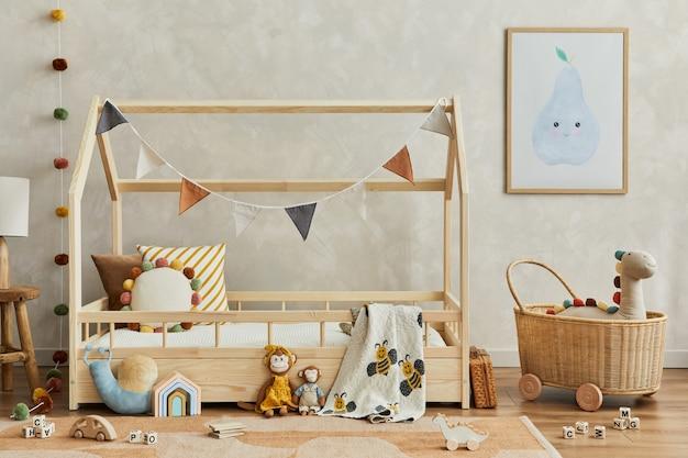 木製のベッド、ぬいぐるみ、木のおもちゃ、籐のバスケット、テキスタイルの吊り下げ装飾が施された、居心地の良いスカンジナビアの子供部屋のインテリアのスタイリッシュな構成。創造的な壁、床のカーペット。レンプレート。