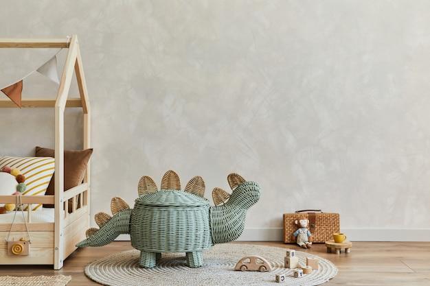 木製のベッド、籐のバスケット、ぬいぐるみ、木のおもちゃ、吊り下げ式の装飾が施された、居心地の良いスカンジナビアの子供部屋のインテリアのスタイリッシュな構成。創造的な壁、床のカーペット。スペースをコピーします。レンプレート。