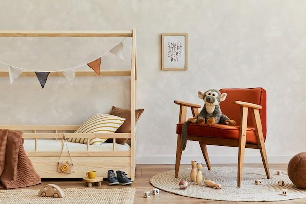 木製のベッド、赤いアームチェア、ぬいぐるみと木のおもちゃ、吊り下げ式の装飾が施された居心地の良いスカンジナビアの子供部屋のインテリアのスタイリッシュな構成。中立的な壁、床にカーペット。スペースをコピーします。レンプレート。