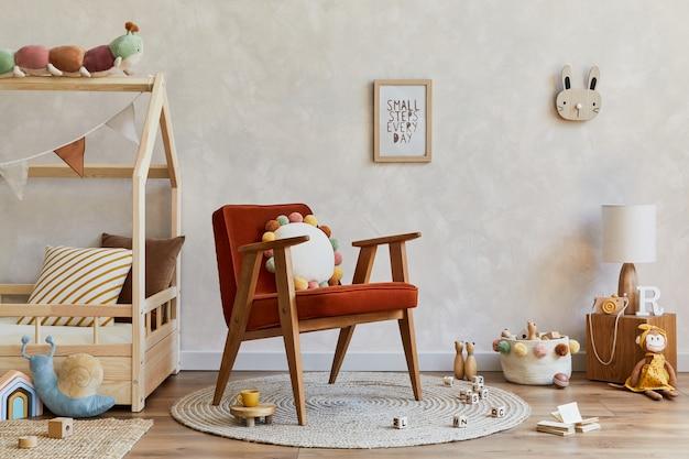 木製のベッド、赤いアームチェア、豪華な木製のおもちゃ、テキスタイルの装飾が施された居心地の良いスカンジナビアの子供部屋のインテリアのスタイリッシュな構成。創造的な壁。スペースをコピーします。レンプレート。