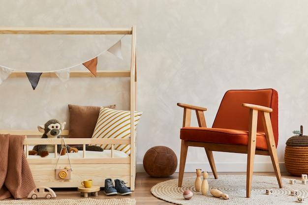 木製のベッド、赤いアームチェア、おもちゃ、テキスタイルの装飾が施された居心地の良いスカンジナビアの子供部屋のインテリアのスタイリッシュな構成。クリエイティブウォールコピースペース。レンプレート。