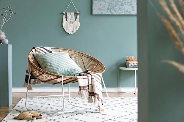 커피 테이블, 등나무 안락 의자, 식물, 카펫 및 아름다운 보호 액세서리가 있는 창의적이고 아늑한 거실 인테리어의 세련된 구성. 유칼립투스 벽과 쪽모이 세공 마루 바닥.